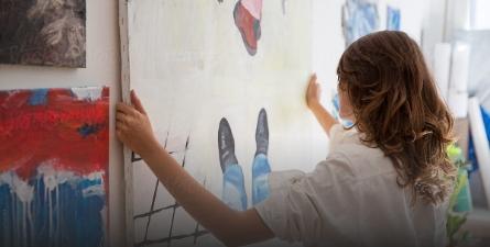 Vrouw hangt schilderij op